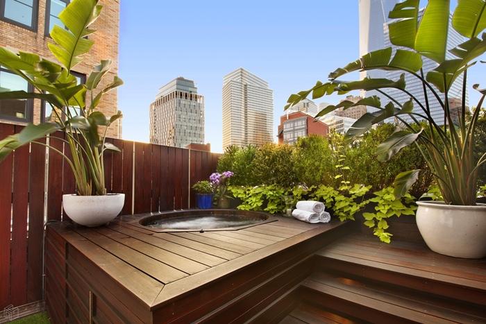 décoration extérieure appartement terrasse en bois pots fleurs blancs plante brise vue serviettes plante fleurie intimité balcon