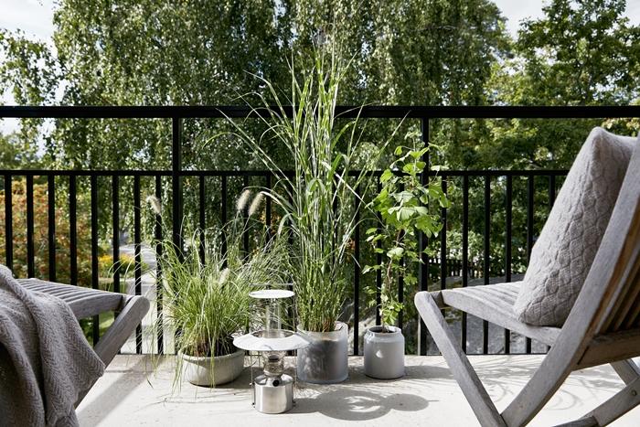 décoration petit balcon extérieur appartement style moderne design chaise bois gris plaid coussin brise vue naturel plantes vertes