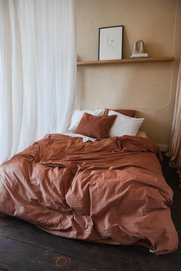 décoration petit espace design minimaliste rêvetement sol bois brut foncé chambre terracotta déco linge de lit étagère bois cadre photo noir