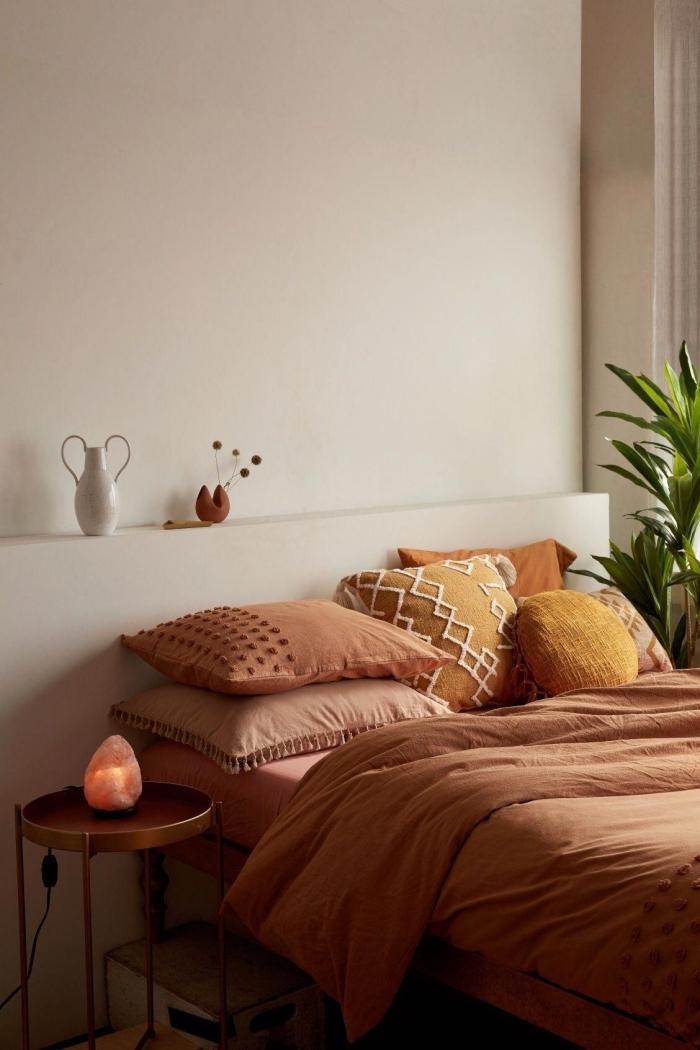 deco couleur terracotta design chambre à coucher boho minimaliste table ronde métal coussin jaune cheddar avec broderie macramé pompons