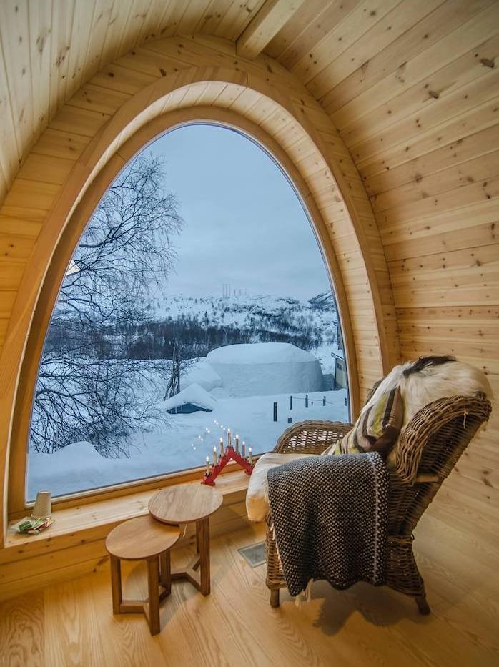 deco salon chaleureux avec fauteuil tressé tables bois gigognes et baie vitrée fenetre avec vue sur paysage enneigé