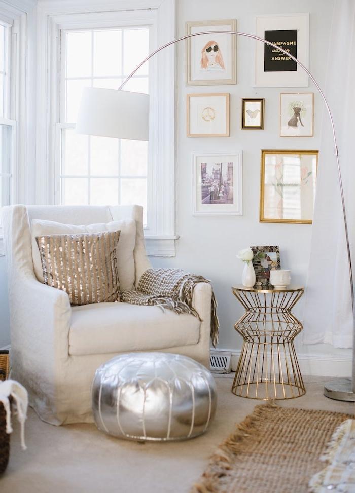 deco sejour avec fauteuil blanc pouf argenté mur décoré de cadres et table en laiton coin lecture coté fenetre