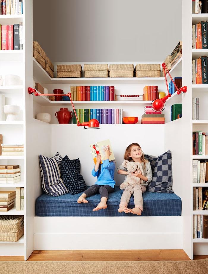 decoration de coin lecture enfant niche murale avec banc à matelas bleu et coussins et bibliotheque murale avec livres