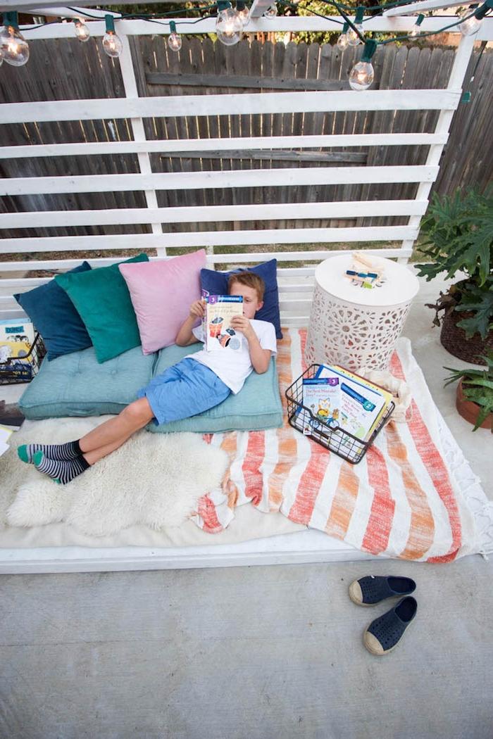exemple comment amenager un coin lecture en plein air avec plusieurs couvertures coussins d assise et coussins colorés et table basse blanche