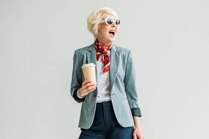 exemple de coiffure femme 60 ans épanouie avec veste grise pantalon gris foncé fichu rouge lunettes de soleil monture blanche