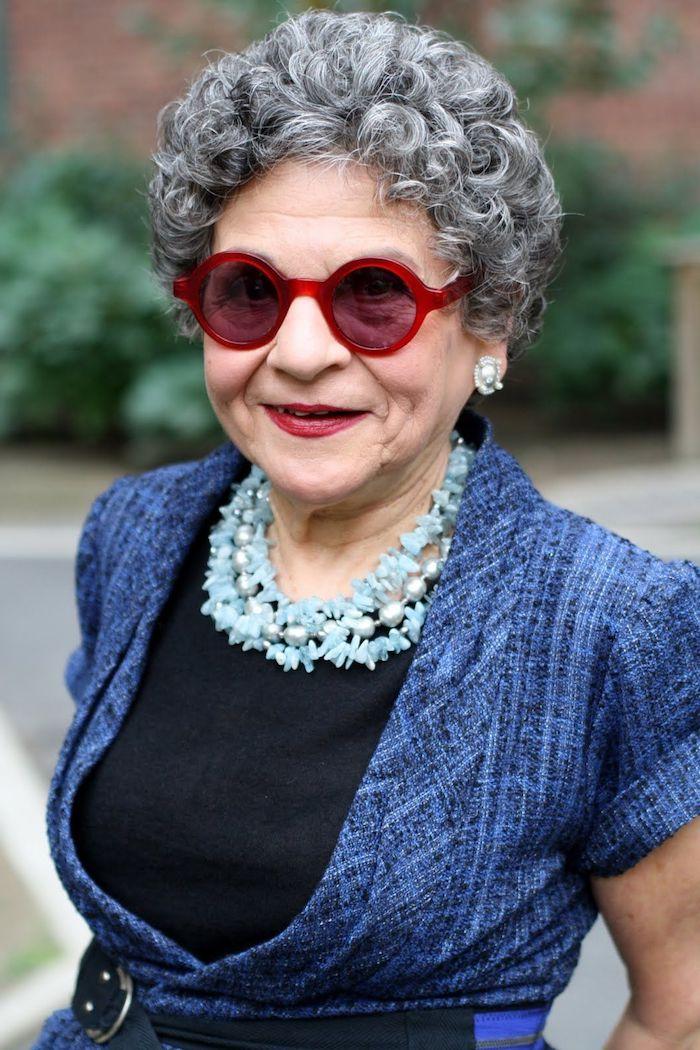 exemple de coupe de cheveux court femme 60 ans avec lunettes monture rouge cheveux gris bouclés collier bleu veste bleue cheveux volumineux
