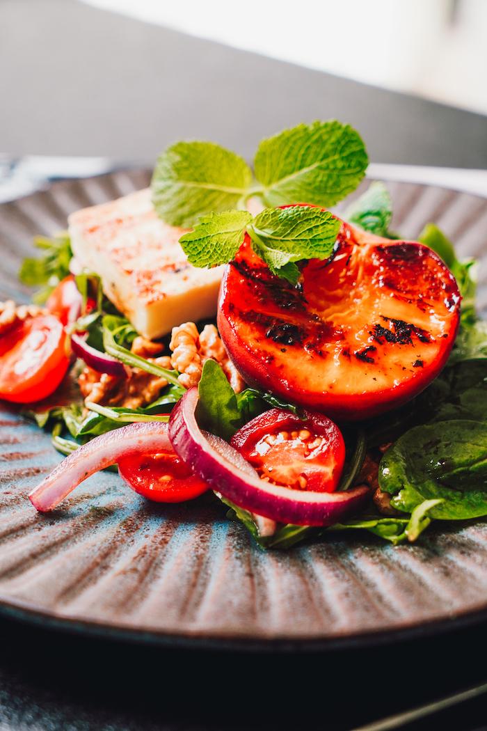 exemple de salade composee excellente avec des épinards roquette pêches oignons rouges noix et halloumi salade originale idée