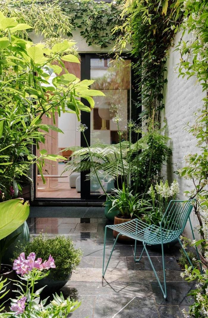 façade maison briques blanches décoration devant maison porte coulissante carrelage chaise métal turquoise brise vue naturel
