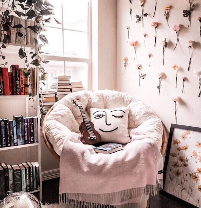 fauteuil confortable pour lire avec couverture gris clair et coussin à visage bibliothèque meuble blanc mur décoré de fleurs fraiche