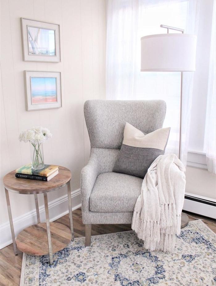 fauteuil lecture gris perle tapis à motifs baroque table en metal et bois à roulettes murs blancs vase de fleurs