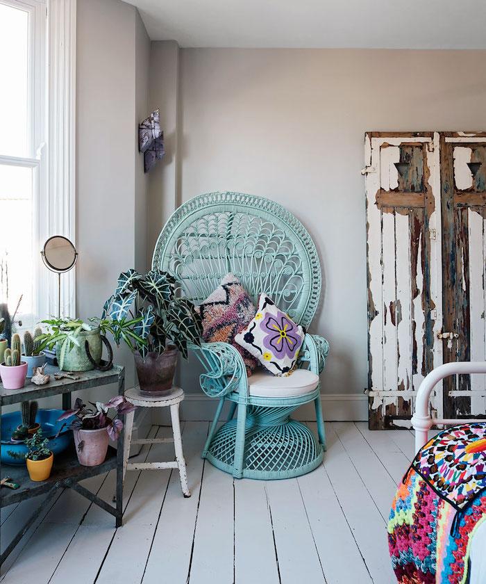 fauteuil oeuf exotique en rotin repeint en bleu avec coussins cosy lit blanc avec couverture orientale colorée et rangement pot de fleurs et armoire vintage chic
