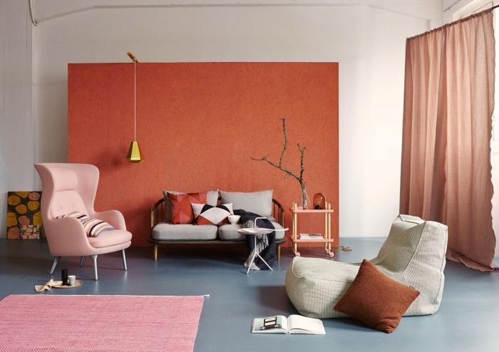 fauteuil rose pastel tapis rose pâle peinture mur terracotta décoration de salon rideaux longs terracotta canapé gris et métal coussin terracotta