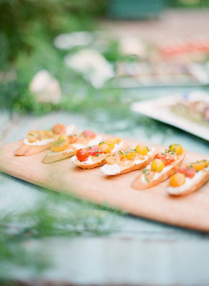 idée crostini recette avec fromage à la crème et des tomates cerise marinés sur plateau de service buffet campagnard idée originale