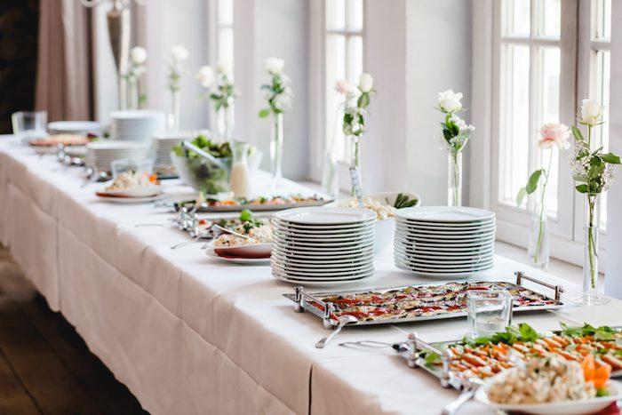idée de buffet de mariage originale avec des plats exquis pile d assiette sur nappe blanche petits bouquets dans soliflores idee repas mariage simple
