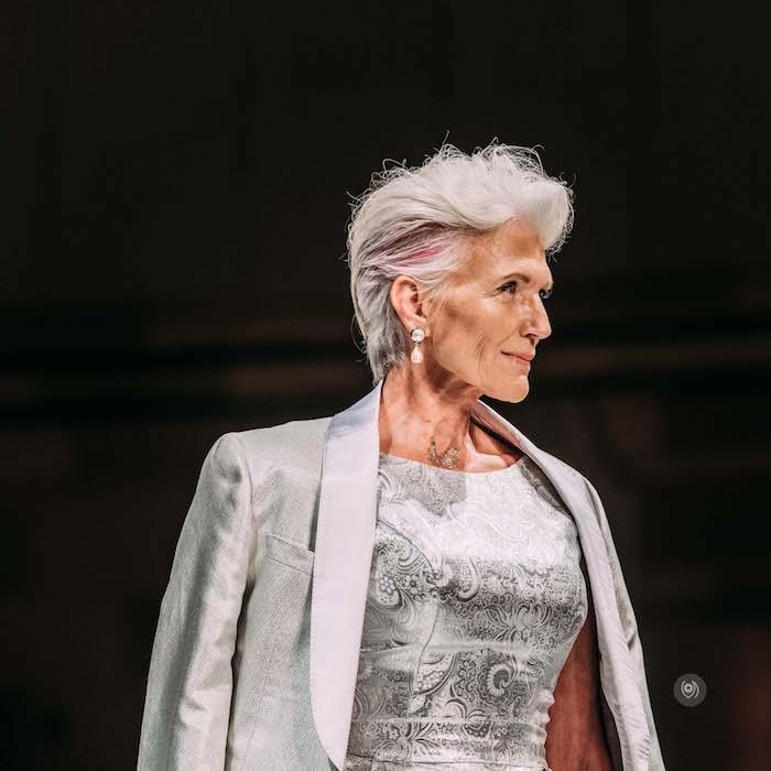 idée maye musk coiffure femme 6o ans épanouie avec une mèche rose et volume sur le dessus robe gris et blanc femme