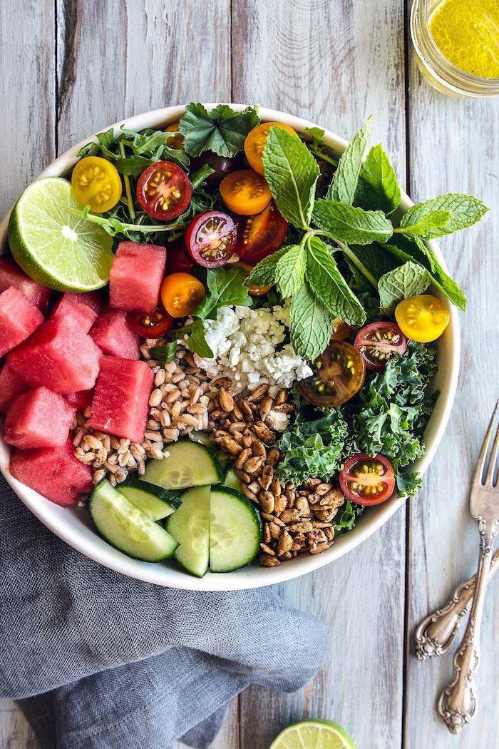 idée repas d été du soir salade composée de chou frisé pasteque roquette concombre tomates et des graines variés avec miettes de feta