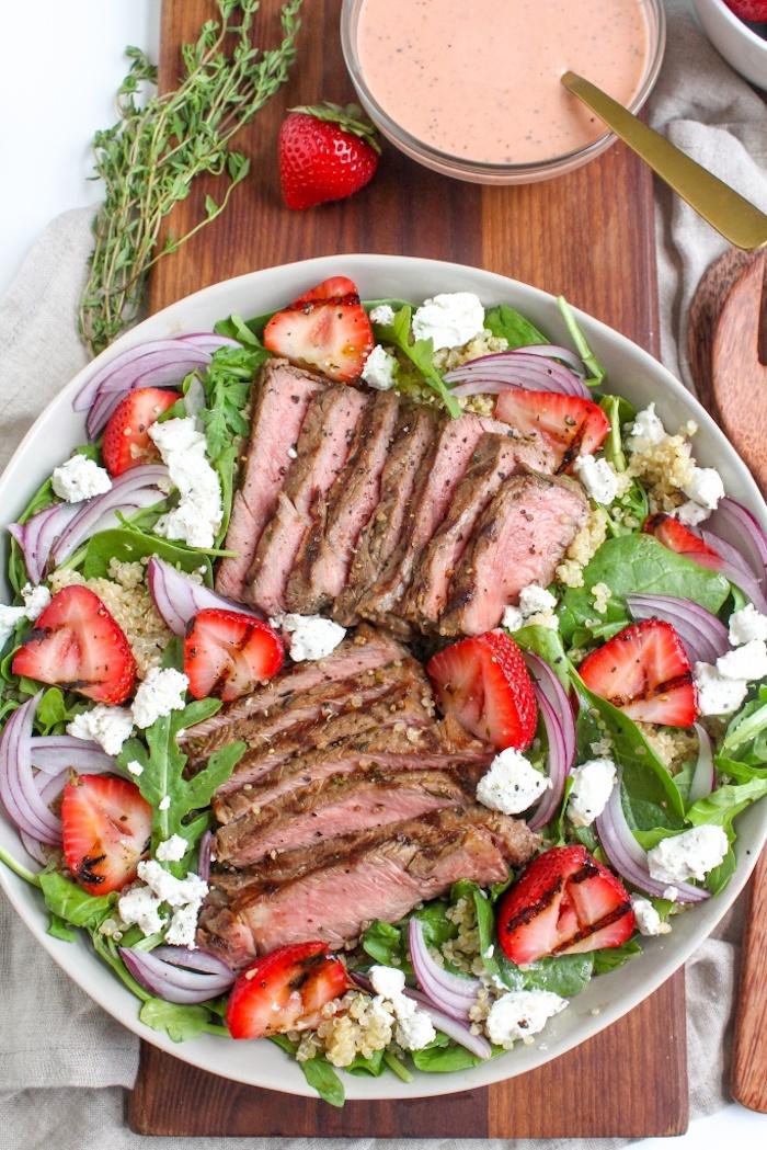 idée repas du soir salade composée à la roquette épinards fraises miettes de fromage feta et steak de porc avec quinoa