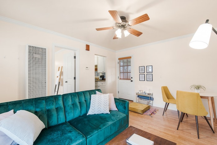 idée ventilateur de plafond avec lumière deco salon canapé bleu turquoise parquet bois clair chaises jaune moutarde