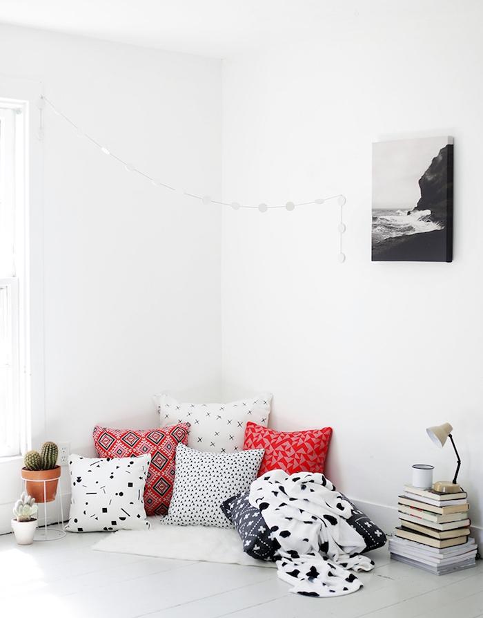 idee deco salon blanc avec coin lecture par sol sur tapis blanc coussins colorés pile de livres par sol et cactus en pot