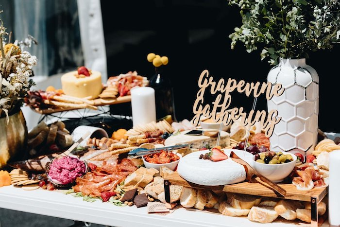 idee grand plateau de fromages charcuterie olives crackets pain de campagne entouré de végétaux sur table bois blanche