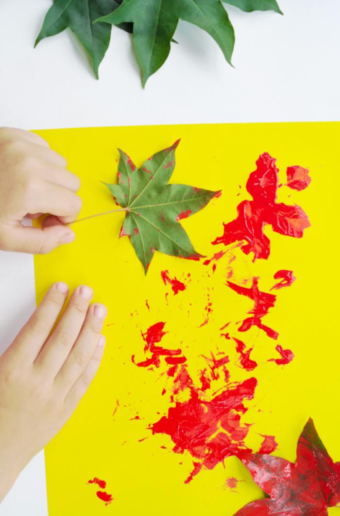laisser des empreintes colorées de feuilles mortes sur un bout de papier jaune activité peinture pour les 2 3 ans