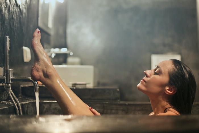 les salles de bains sombres ont encore plus besoin de ventillation femme dans le baignoire