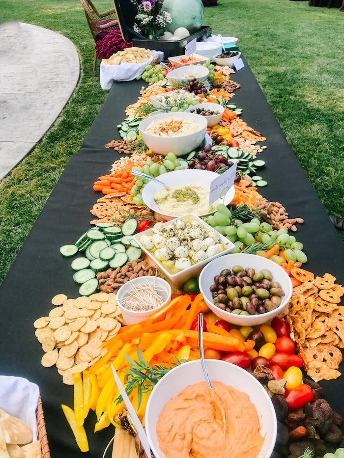 longue table de crudités bretzels crackets biscuits salés fruits et légumes frais avec des noix sur table avec nappe noire