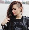 look rock feme avec des cheveux lonf ondulés et côtés rasé tee tenue femme noire style rock