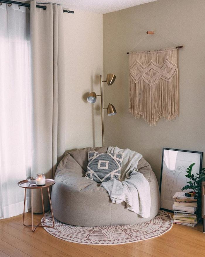 macramé mural avec pouf canapé gris clair pile de livres et table minimaliste rose gold deco scandinave