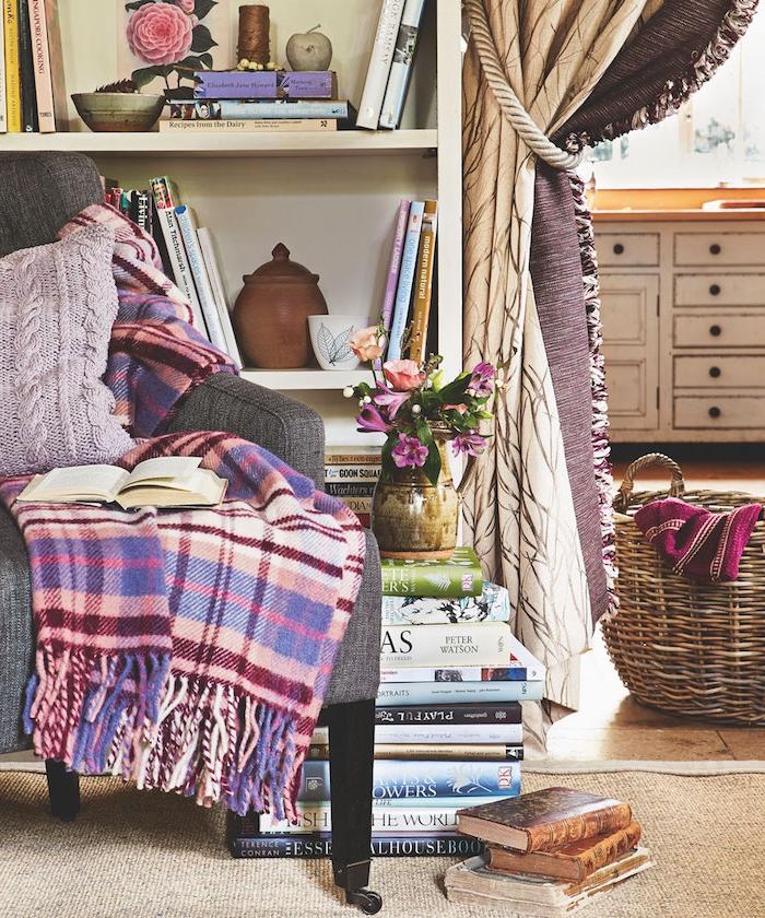 meuble bibliotheque à coté de coin bibliothèque avec vase fleuri et canapé gris avec couverture colorée et coussin housse maille violette panier de rangement rotin