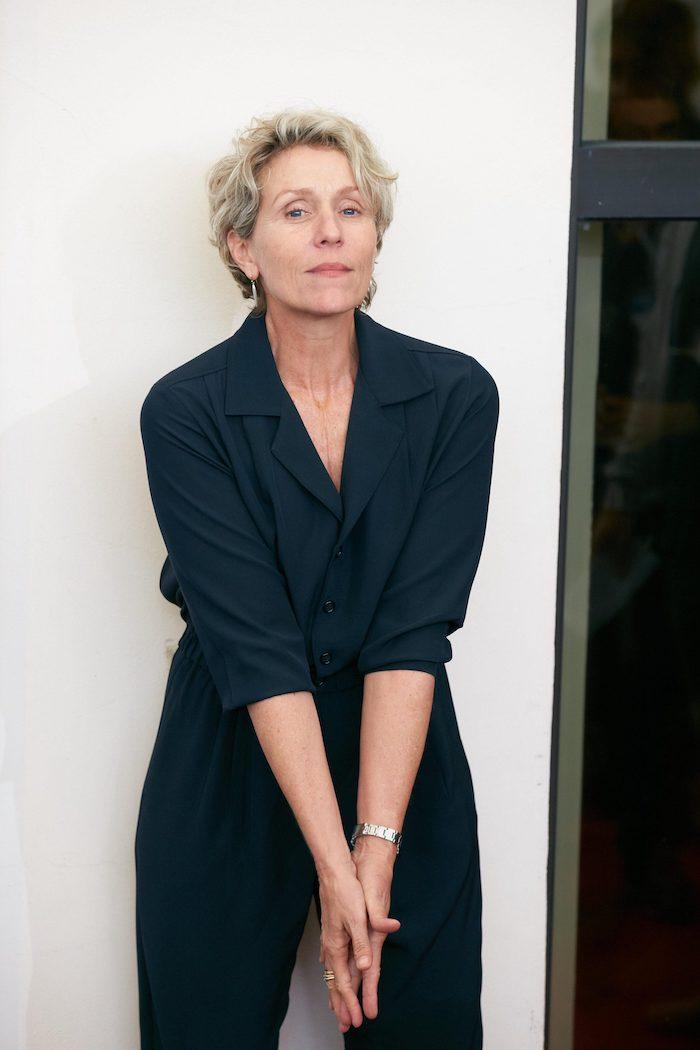 modèle coupe courte femme aux cheveux gris bouclés pixie bouclé tailleur femme couleur bleu marine