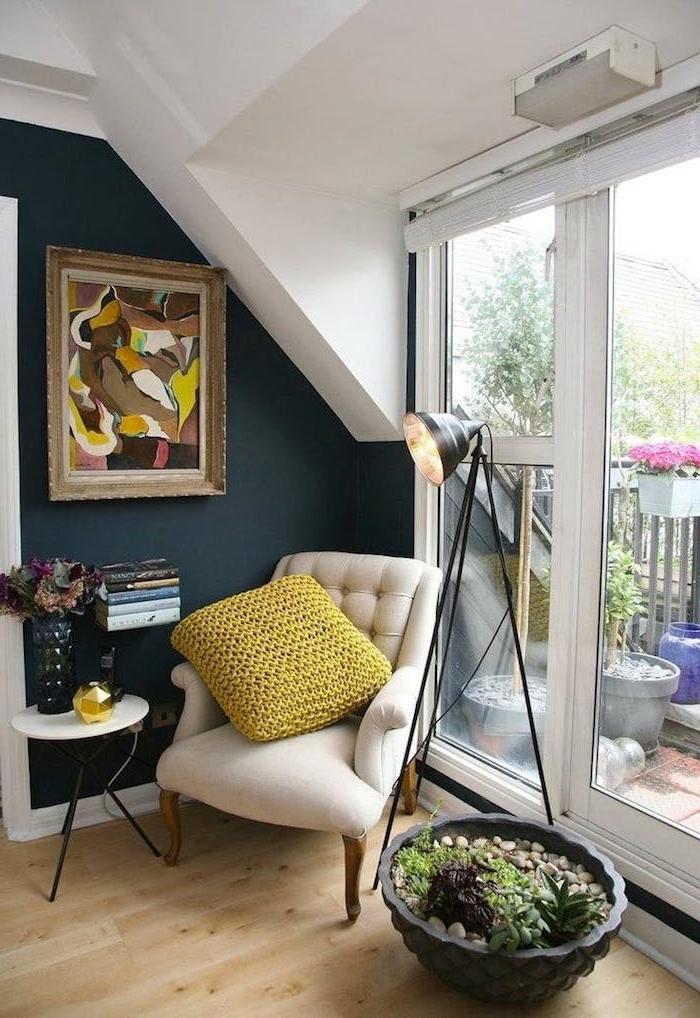 mur bibliothèque flottante petite taille avec fauteuil blanc cassé et mur bleu gris avec cadre art coloré et grand pot jardin interieur