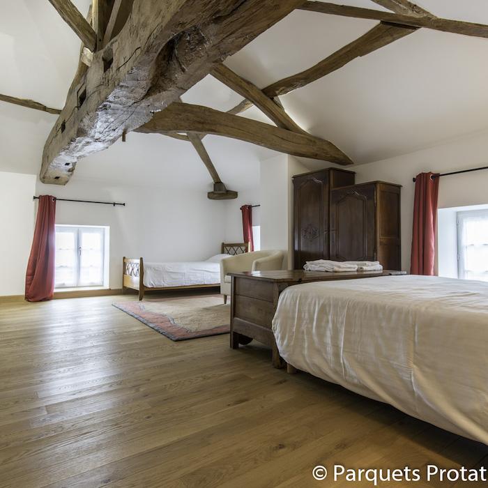 parquet en bois massif pour aménager une chambre rustique avec mobilier de bois brut et des murs blancs