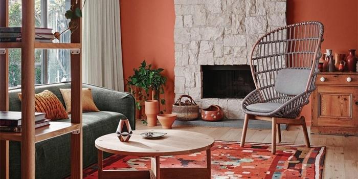 peinture couleur terracotta décoration salon bohème moderne canapé vert de gris chaise rotin table ronde basse plante verte cheminée