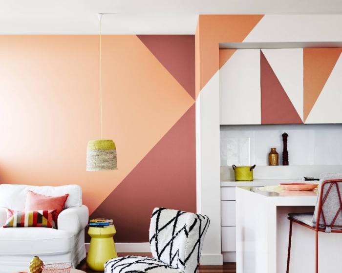 peinture couleur terracotta design salon moderne ouvert vers petite cuisine blanche crédence îlot fauteuil blanc et noir suspension lampe jaune
