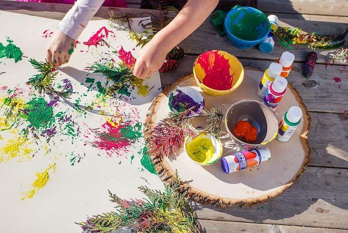 peinture enfant sur toile avec des branches de pin et des peintures de couleurs variées idee jeu en plein air enfant vacances été