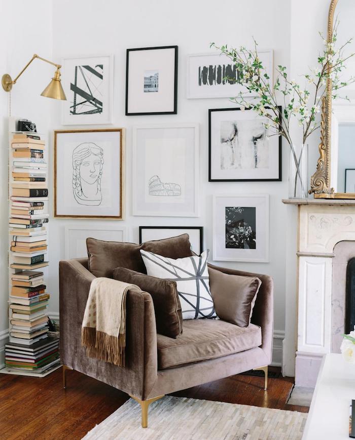 pilepdeplibres bobliotheque verticale fauteuil gris parquet bois brut mur de cadres d art noir et blanc cheminée baroque