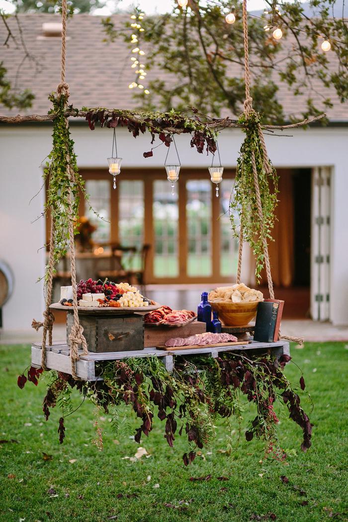 presentation buffet froid deco avec table palette syspendue et fleurie plateaux charcuterie chips fromages fruits salami