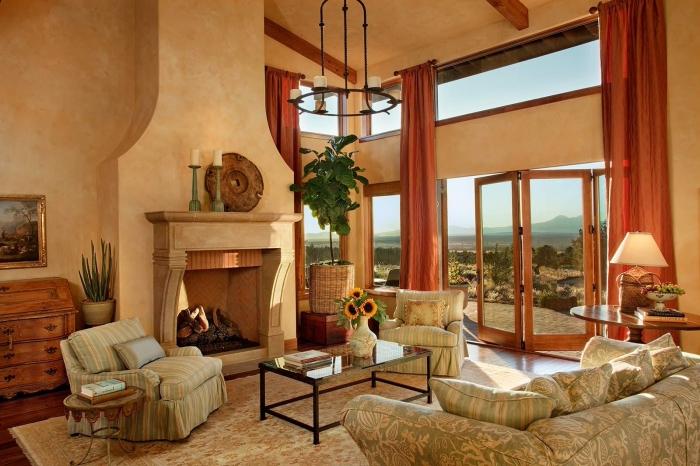 rideau terracotta long décoration salon couleur pêche canapé damassé floral cheminée meubles en bois plante verte table basse verre et métal