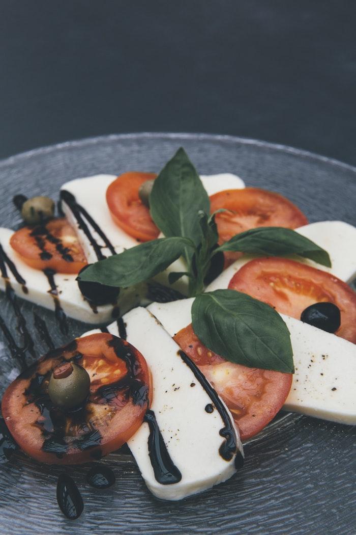 salade caprese à la mozzarella avec des rondelles de tomate basilic et reduction de vinaigre de balsamique
