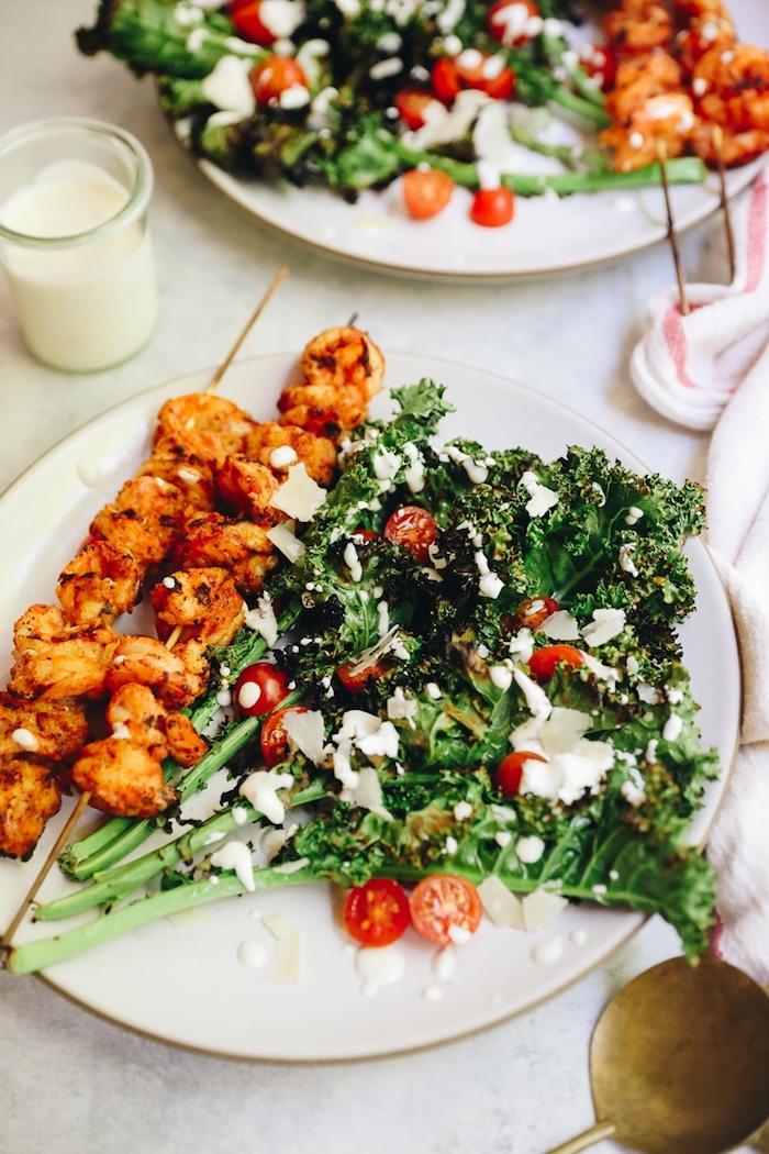 salade cesar au kale avec du parmesan et tomates cerise et brochettes de crevette grillées à la panure salade de saison estivale