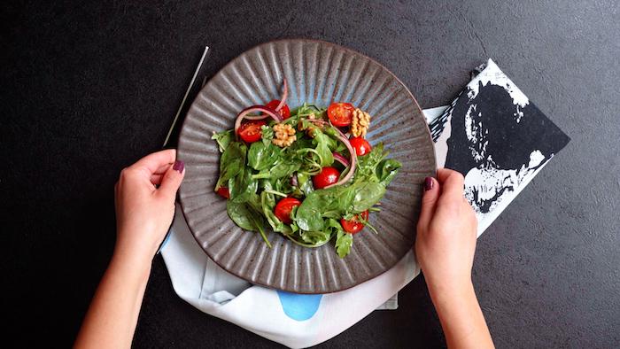 salade composee excellente roquette épinards tomates cerises noix dans une assiette idee que repas de midi salade