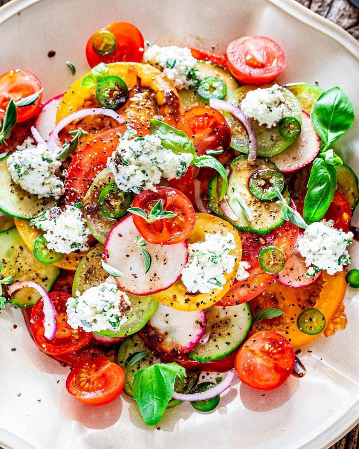 salade de tomates de couleurs variées au basilic avec fromage ricotta aux herbes fraiches et reduction de vinaigre de balsamique