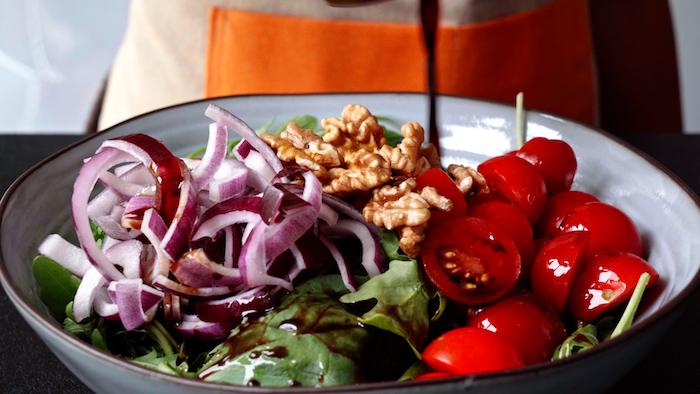salade printemps été simple verser vinaigrette pour épicer salade roquette et épinards avec tomates cerises et oignons rouges