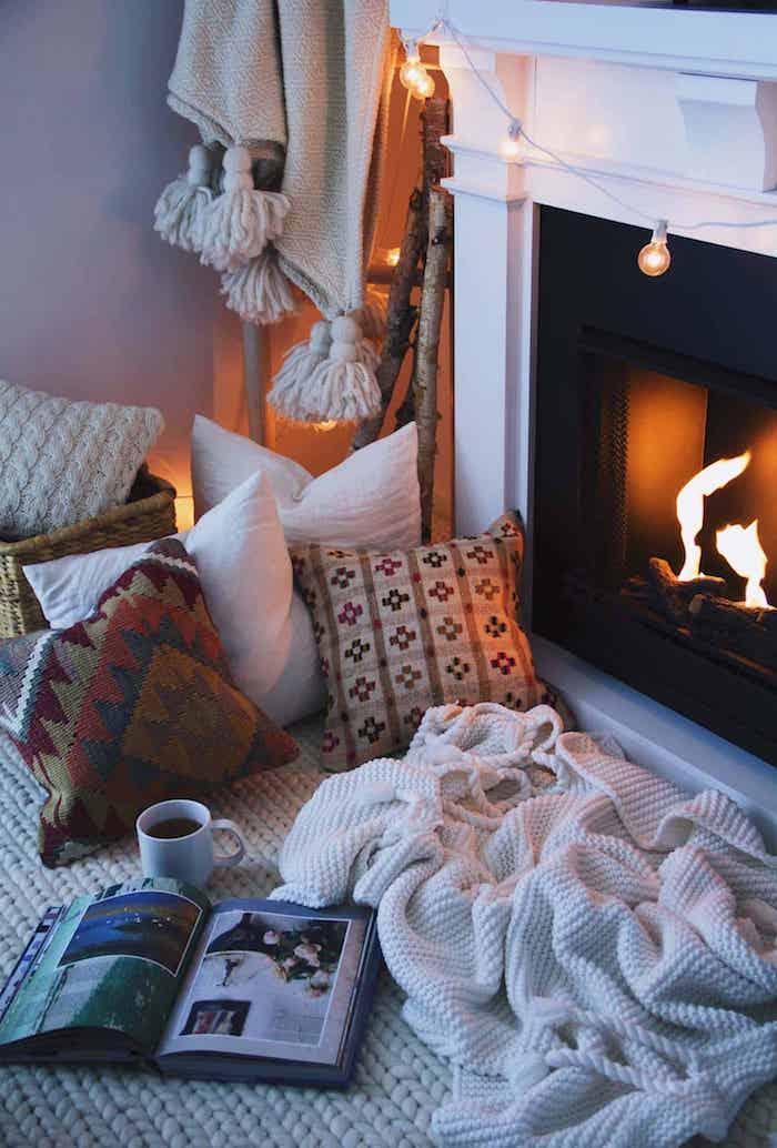 salon cocooning deco cosy coin lecture côté cheminée couverture blanche coussins colorés cheminée design moderne