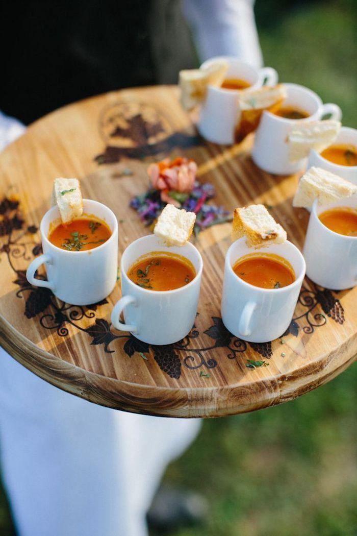 soupe froid dans une tasse à café avec basilic frais et tranche de pain sur planche de bois avec des légumes au centre