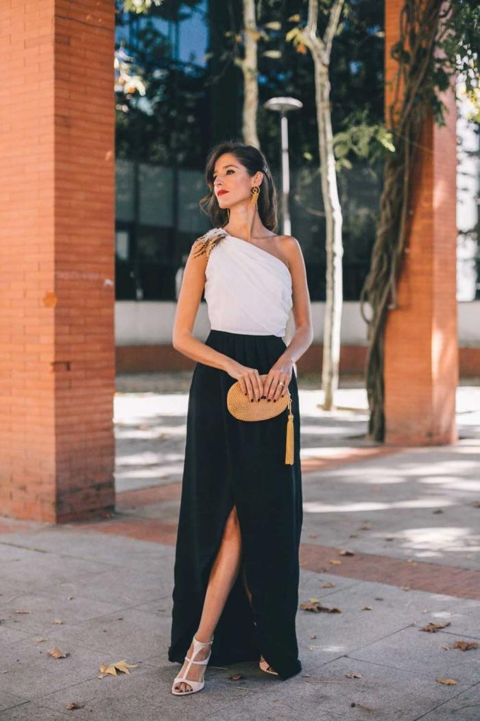 tenue femme classe élégante robe longue pour mariage top blanc col asymétrique jupe noire fendue taille haute sac à main paille