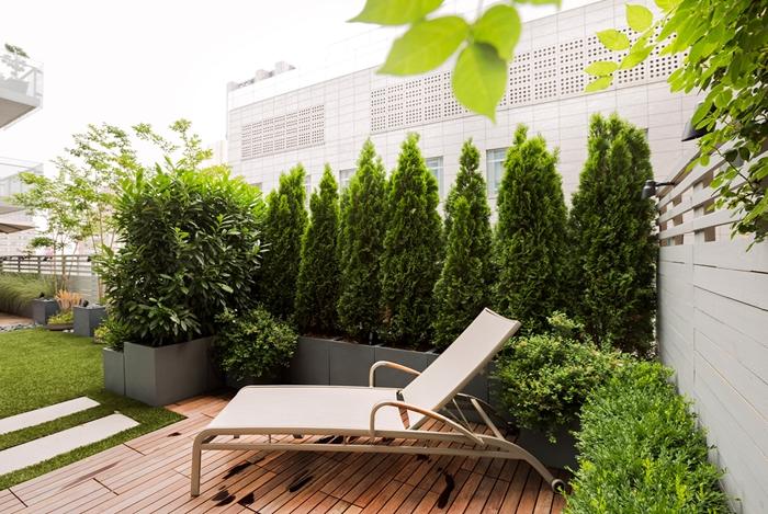 transat jardin aménagement petite terrasse en bois haie végétale conifère gros pots fleurs gris plantes vertes arbres mur végétal