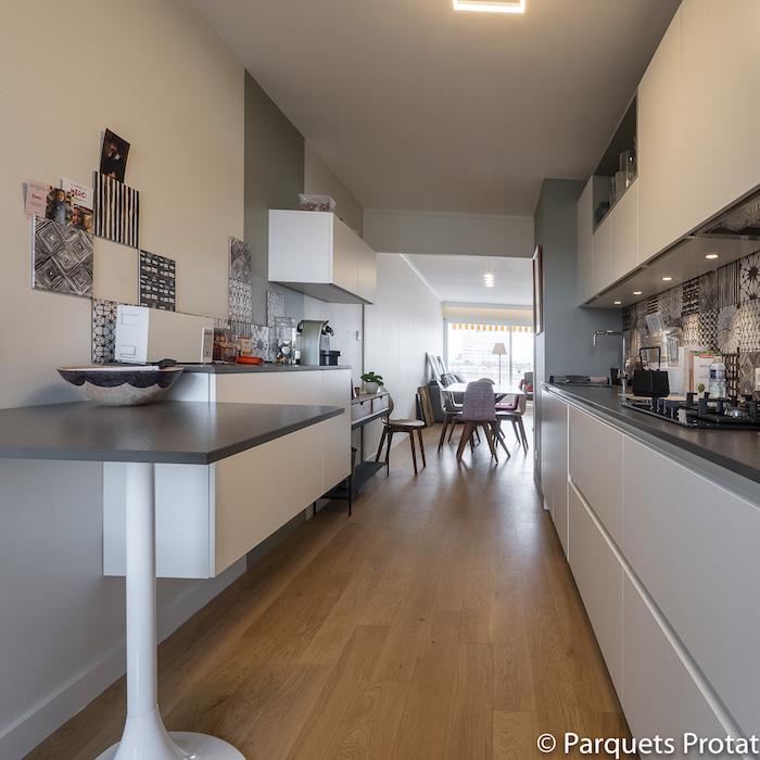 un parquet en bois massif pour toutes les pièces de la maison cuisine blanc et gris avec parquet clair deco cuisine ouverte sur salle à manger salon