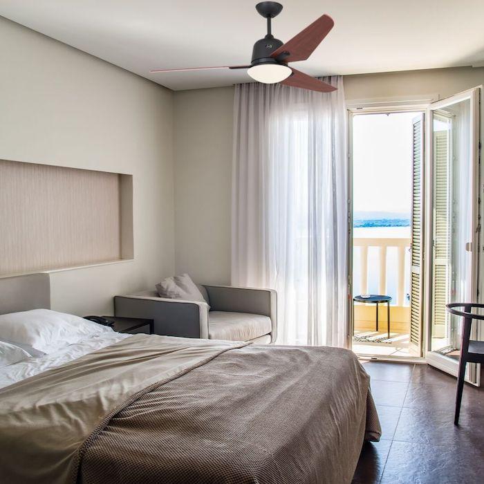 ventilateur plafond silencieux avec lumière dans une chambre adulte moderne carrelage sol marron linge de lit marron beige et blanc